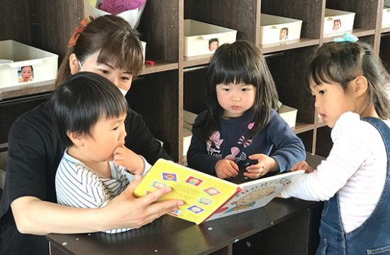 本を読む子どもと保育士